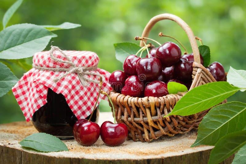Krus av driftstopp och korg av söta körsbär i trädgård utomhus arkivfoton