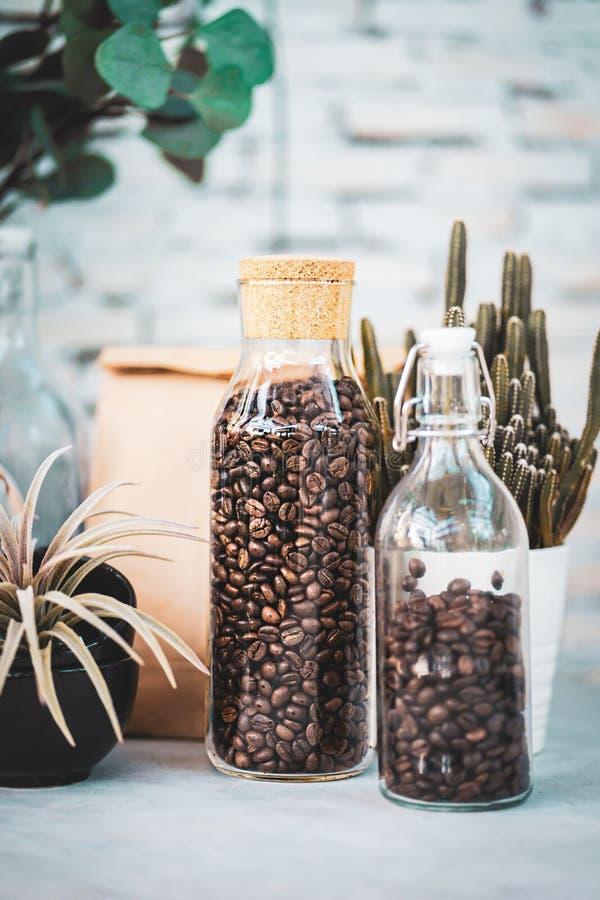 Krus av exponeringsglas med ett vinkorklock med kaffebönor på gammal träräknare royaltyfria foton