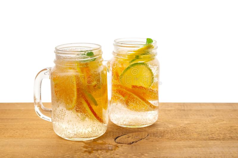 Krus av hemlagad lemonad med den skivade nya citronen, apelsinen, limefrukt, fattar mintkaramellen och bubblor på isolerad träbak royaltyfri foto
