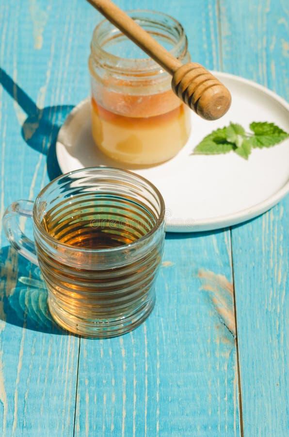 Krus av honung med den genomblöta skeden i en platta och en exponeringsglaskopp te p? en bl? tr?tabell arkivbild