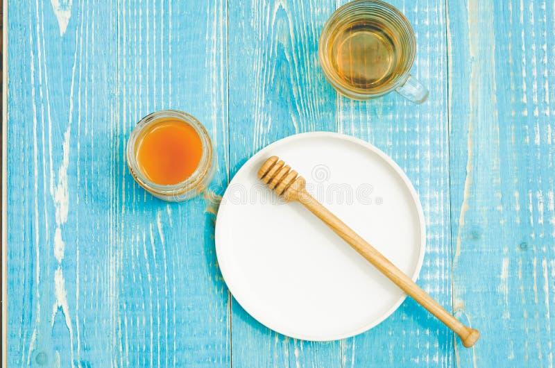 Krus av honung med den genomblöta skeden i en platta och en exponeringsglaskopp te p? en bl? tr?tabell Top besk?dar royaltyfria bilder