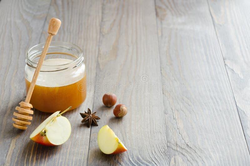 Krus av honung med honungpinnen, skivor av äpplet, hasselnötter och anis fotografering för bildbyråer