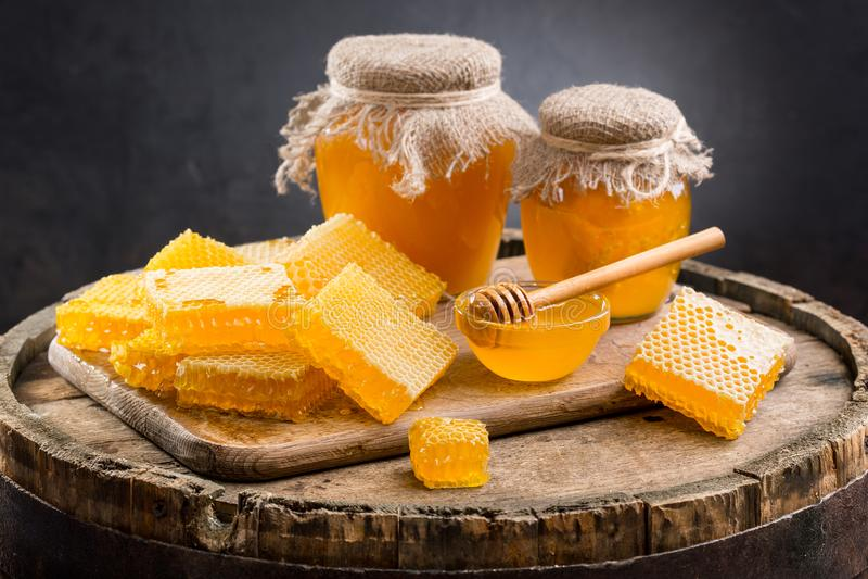 Krus av honung och honungskakor arkivbilder