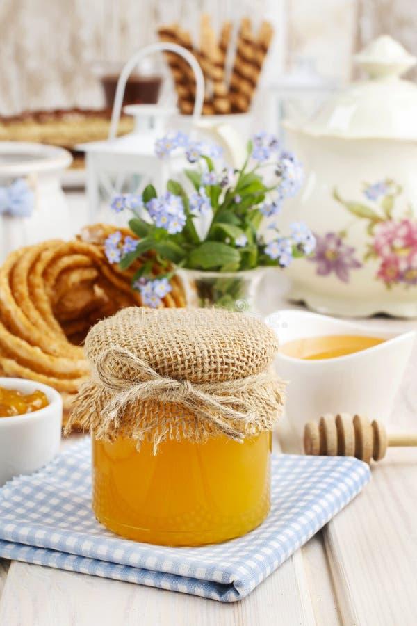 Krus av honung på frukosttabellen royaltyfria bilder