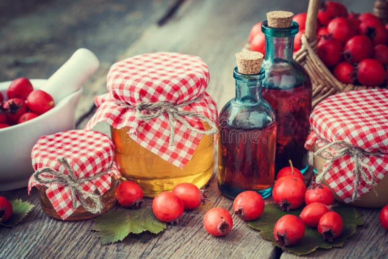 Krus av honung, tinkturflaskor och mortel av hagtornbär arkivbild