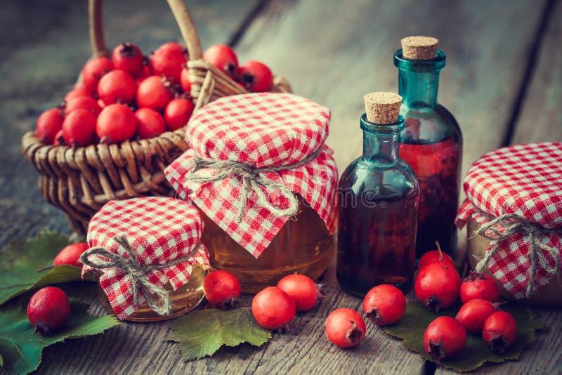 Krus av honung, tinkturflaskor och mortel av hagtornbär royaltyfri fotografi