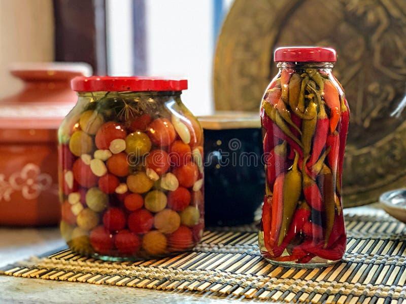 Krus av inlagda peppar och tomater som är hemlagade arkivfoton