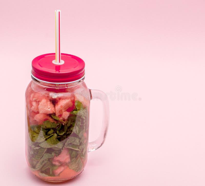 Krus av kall ny lemonad med stycket av vattenmelon och drickasugrör på rosa bakgrund arkivbilder