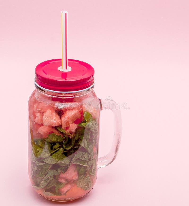 Krus av kall ny lemonad med stycket av vattenmelon och drickasugrör på rosa bakgrund arkivbild