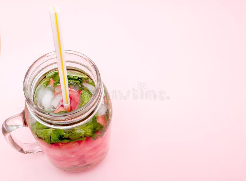 Krus av kall ny lemonad med stycket av vattenmelon och drickasugrör på rosa bakgrund arkivfoton