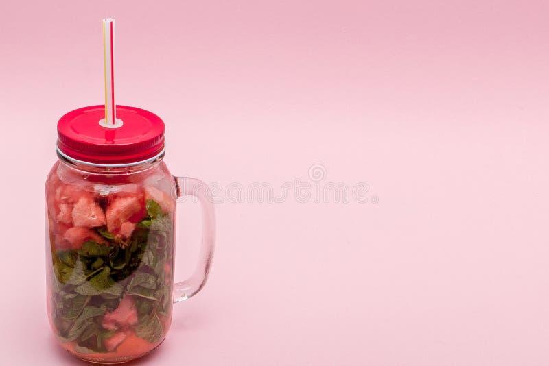 Krus av kall ny lemonad med stycket av vattenmelon och drickasugr?r p? rosa bakgrund royaltyfri fotografi