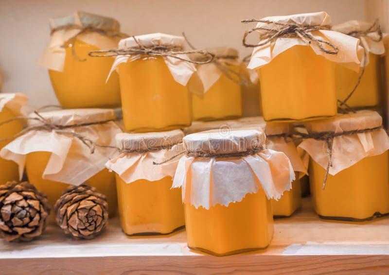 Krus av kanderad limefrukthonung på hyllan shoppar in Sale av naturlig honung i marknad Produktion av honung royaltyfria bilder