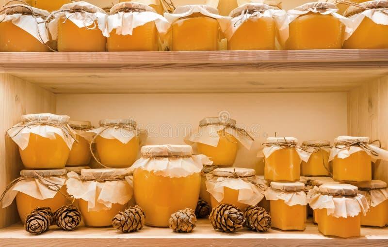 Krus av kanderad limefrukthonung på hyllan shoppar in Sale av naturlig honung i marknad Produktion av honung arkivfoton