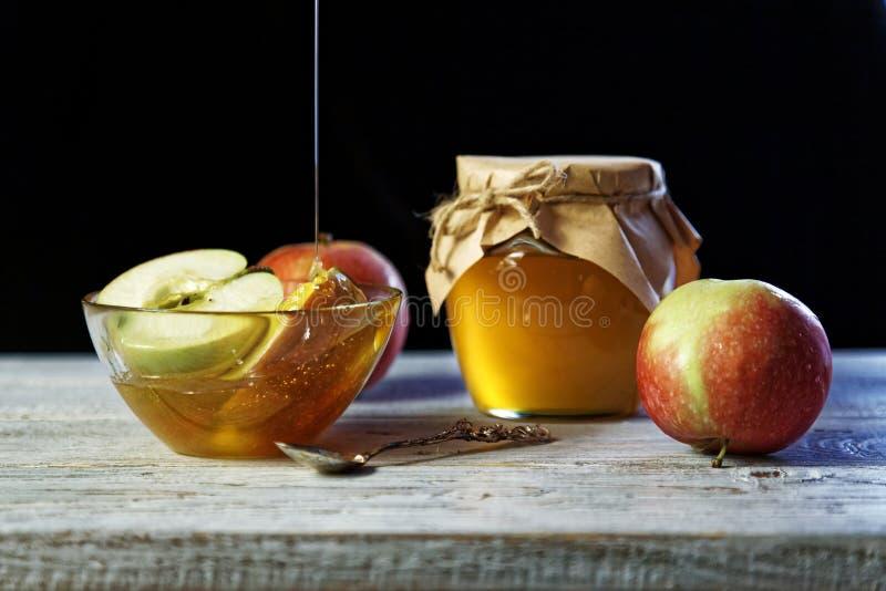 Krus av lantlig honung och och äpplen på trätabellen Traditionell berömmat för det judiska nya året Begrepp Rosh Hashana royaltyfria bilder