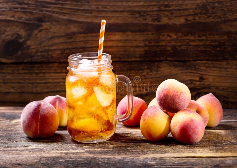 Krus av med is te för persika arkivbilder