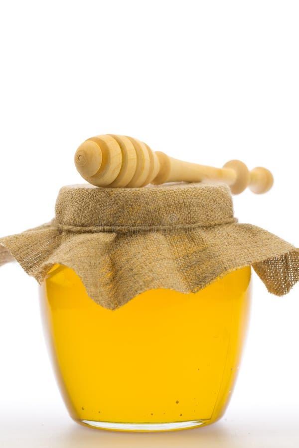 Krus av ny honung med drizzler som isoleras på vit bakgrund arkivfoto