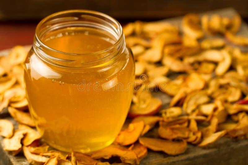 Krus av ny honung med torkade äpplen på träbakgrund royaltyfri bild