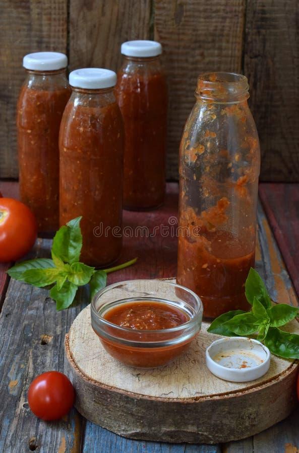 Krus av tomatsås med chili, peppar och basilika Bolognese sås, passata, lecho eller adjika bevarande canning royaltyfri foto