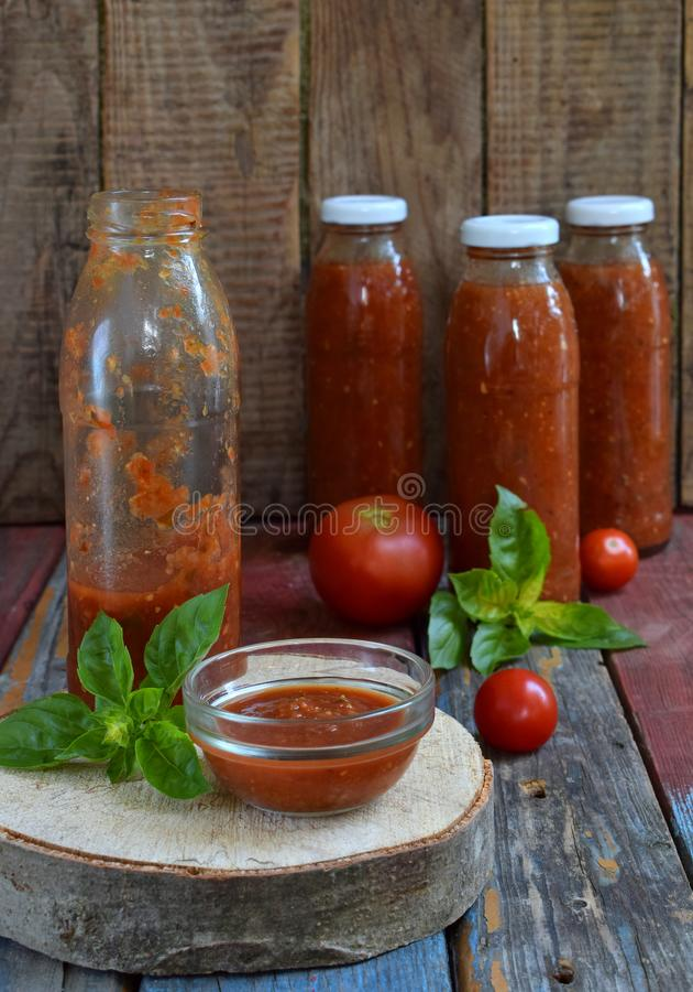 Krus av tomatsås med chili, peppar och basilika Bolognese sås, passata, lecho eller adjika bevarande canning royaltyfria bilder