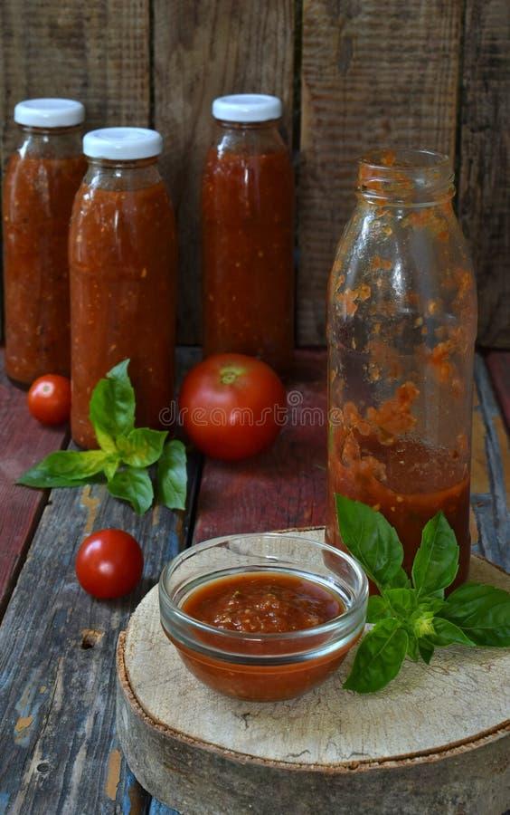 Krus av tomatsås med chili, peppar och basilika Bolognese sås, passata, lecho eller adjika bevarande canning arkivfoton