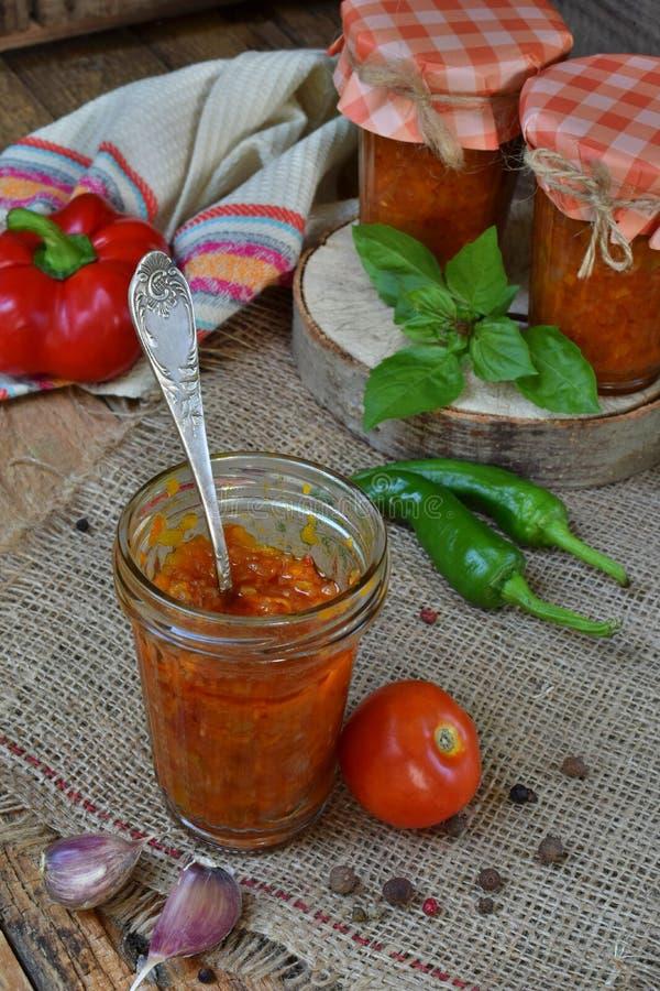Krus av tomatsås med chili, peppar och vitlök Bolognese sås, lecho eller adjika bevarande canning arkivfoto