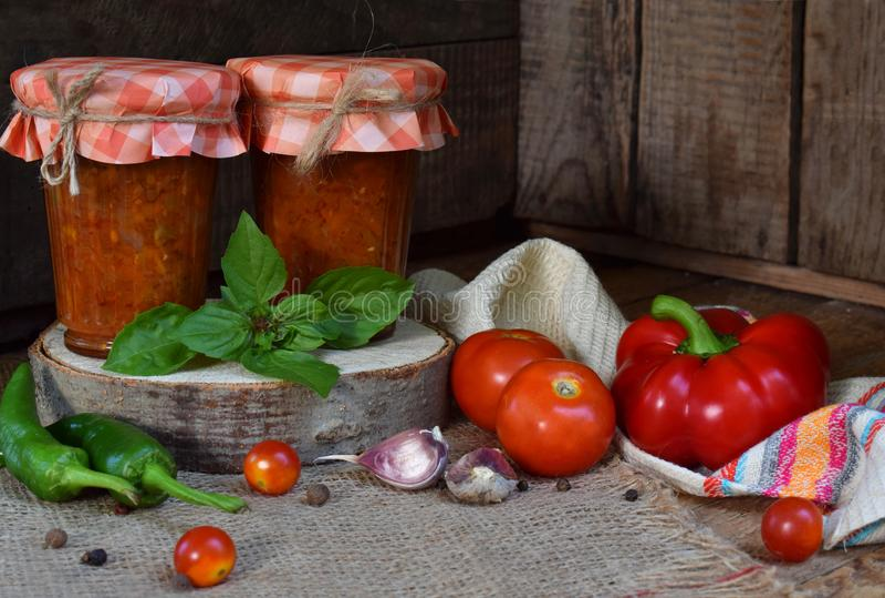 Krus av tomatsås med chili, peppar och vitlök Bolognese sås, lecho eller adjika bevarande canning royaltyfri foto