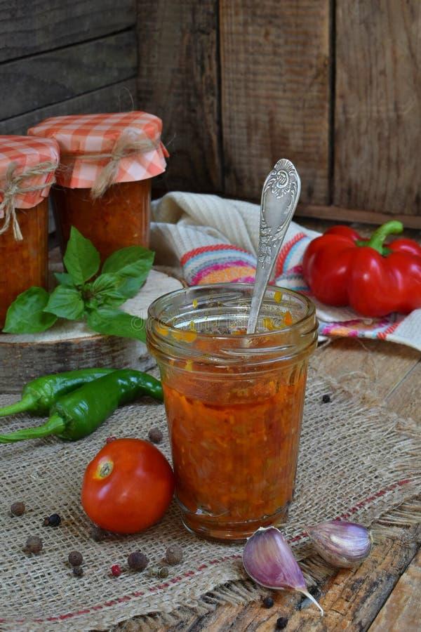 Krus av tomatsås med chili, peppar och vitlök Bolognese sås, lecho eller adjika bevarande canning royaltyfria foton