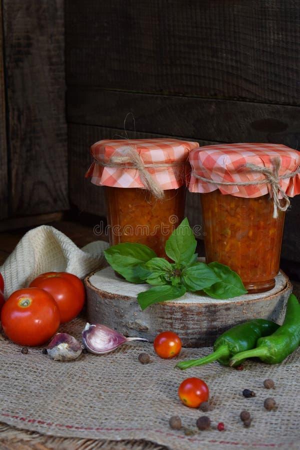 Krus av tomatsås med chili, peppar och vitlök Bolognese sås, lecho eller adjika bevarande canning arkivbild