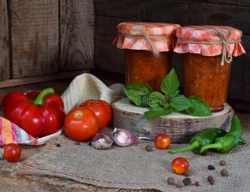 Krus av tomatsås med chili, peppar och vitlök Bolognese sås, lecho eller adjika bevarande canning arkivfoton