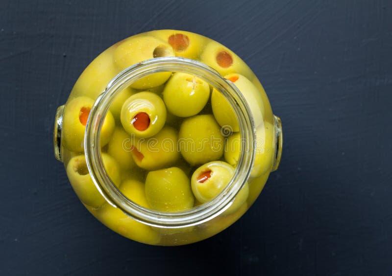 Krus av välfyllda gröna oliv i saltvattenslut upp fotointelligens för bästa sikt arkivbild