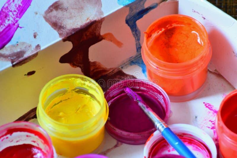 Krus med färgrika ljusa färger och en borste är förberedda för arbetet för konstnär` s arkivfoto