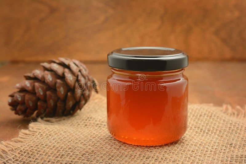 Krus med honung på grovt tyg med en kotte mot bakgrunden av en träbordsskiva fotografering för bildbyråer