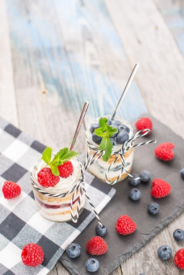 Krus med ny yoghurt och bär på tabellen fotografering för bildbyråer