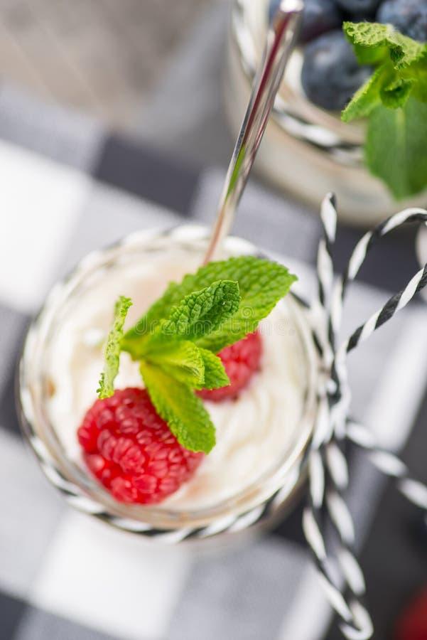 Krus med ny yoghurt och bär på tabellen royaltyfria foton