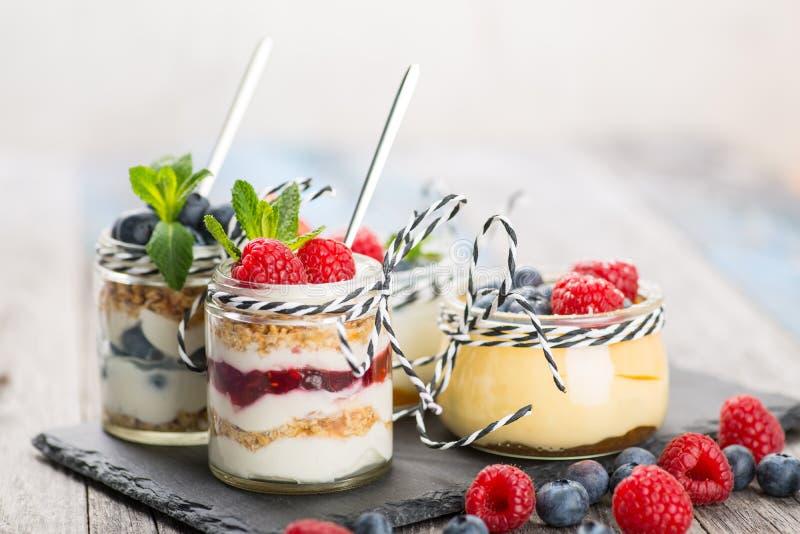 Krus med ny yoghurt och bär på tabellen royaltyfri bild