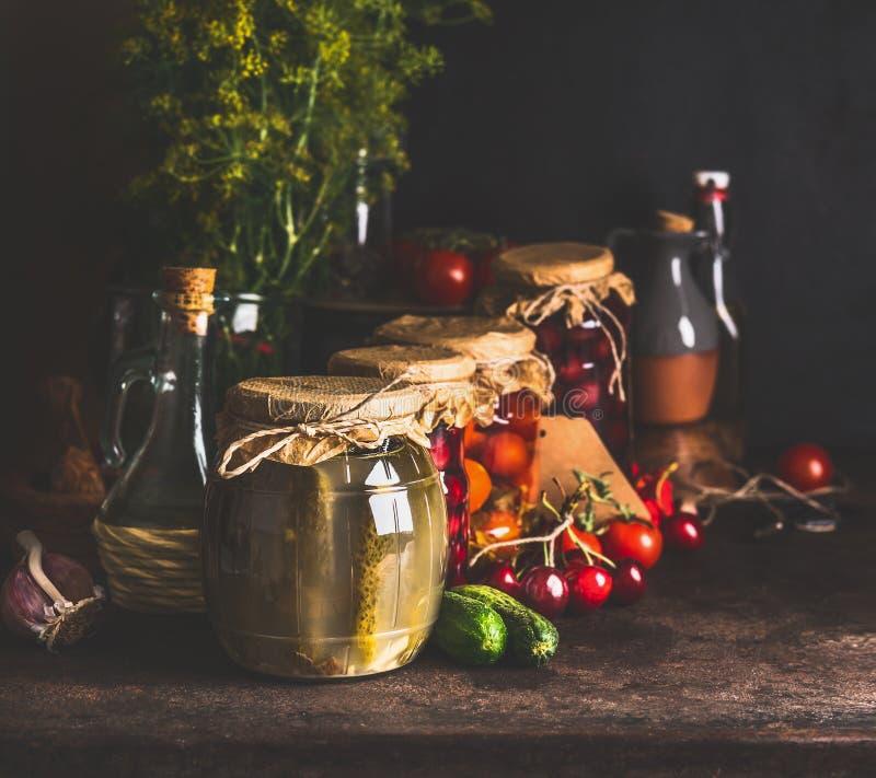 Krus med variation av traditionella bevarade jäste organiska säsongsbetonade grönsaker och frukter för lantgård på mörk lantlig b royaltyfria bilder