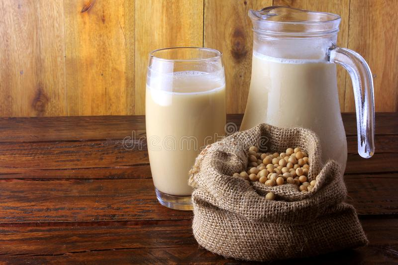 Krus- och exponeringsglaskoppen med nya sojabönor mjölkar och korn i en lantlig påse på trätabellen Bekl?da besk?dar fotografering för bildbyråer