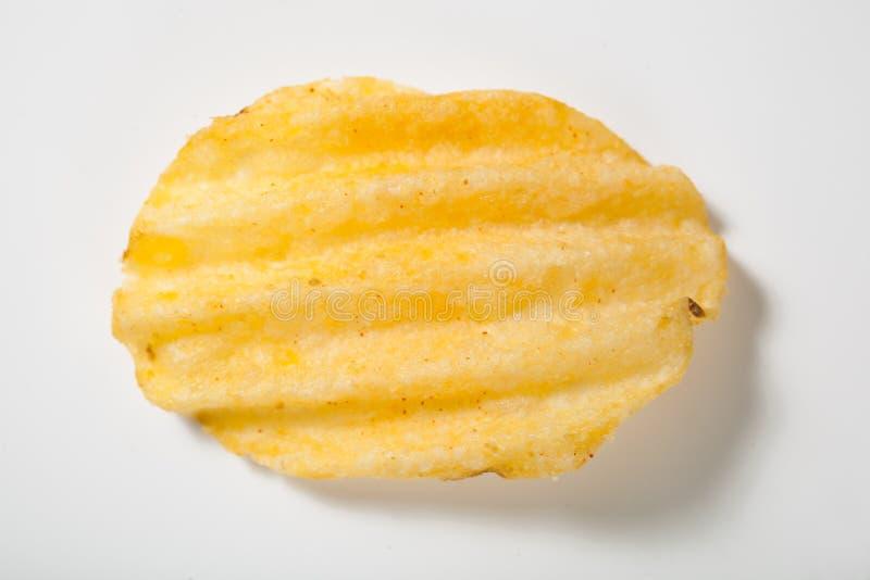 Krusig potatischip på vit arkivbild