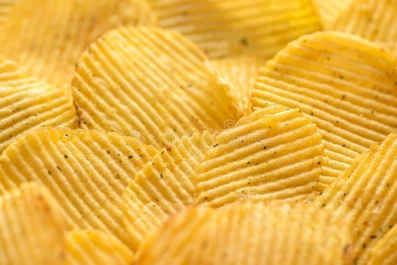 krusiga naturliga potatischiper med salt och grönska arkivfoton