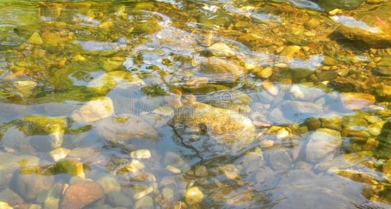 Krusningar av kristallklart vatten reflekterar ljus på sötvatten över kiselstenar och stenar på vattenfallet i Thailand för bakgr arkivbilder
