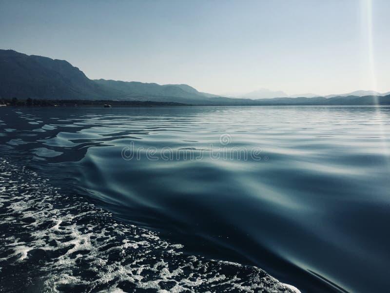 Krusningar i vaken av ett pontonfartyg på soluppgång på en sjö i Turkiet royaltyfria bilder