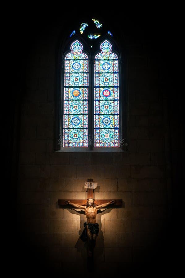 Kruzifix in der Kirche unter Buntglasfenster. lizenzfreies stockfoto