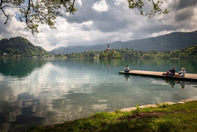 Krwawiący, Slovenia, Maj - 18, 2019: ludzie cieszy się pięknego widok na jeziorze, siedzi i kłama na drewnianym footbridge Krwawi obrazy stock