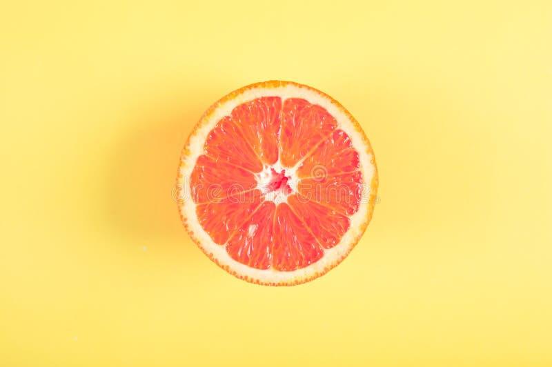 Krwista pomarańczowa owoc na koloru żółtego barwionym tle zdjęcia stock