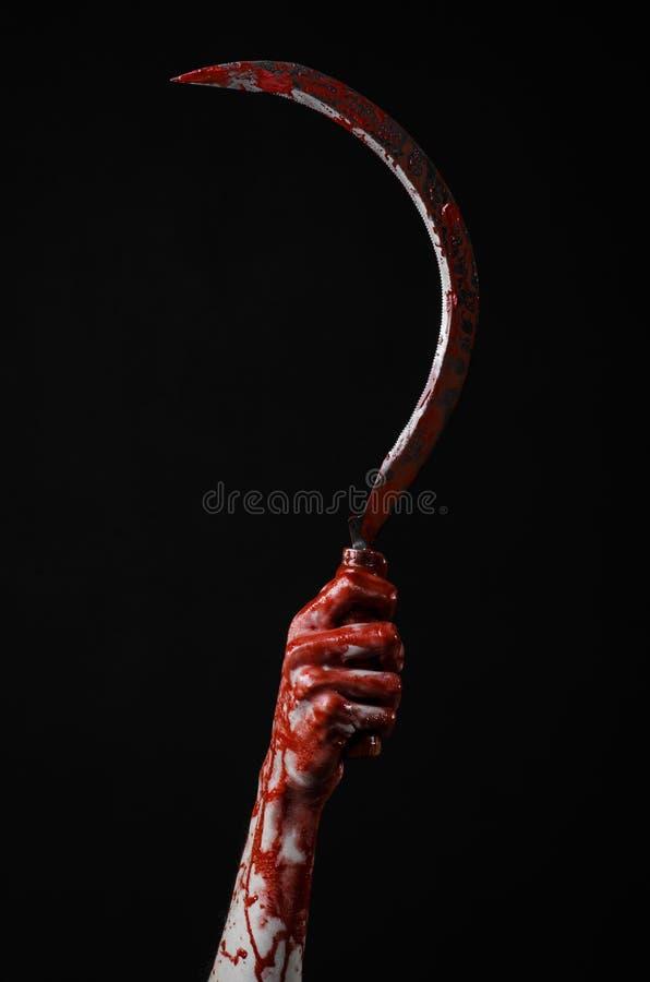 Krwista ręka trzyma sierpa, sierp krwisty, krwista kosa, krwisty temat, Halloween temat, czarny tło, odizolowywający fotografia royalty free