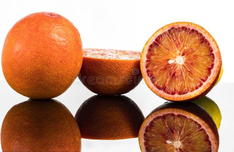 Krwisty pomarańczowy cały i połówki, plasterki z odbiciem na białym i czarnym tle w kiści woda obraz royalty free