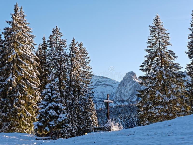 Krycifixionminnen mellan fira träd och snöalpina landskap på vintern arkivbilder
