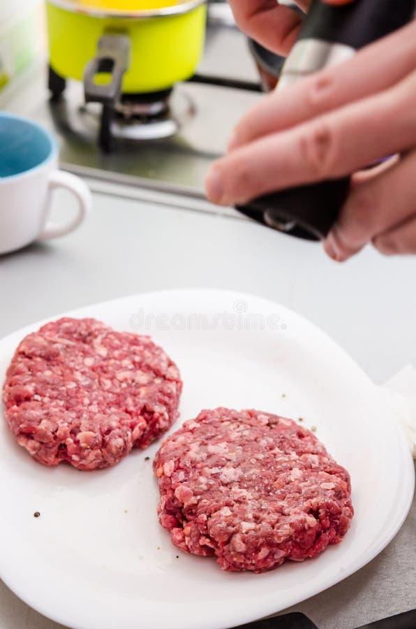 Krydda den rå hamburgaren arkivbilder