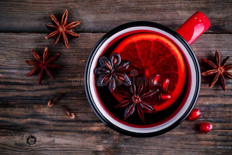 Kryddad granatäppleäppelcider funderade vinsangria i rött rånar på träbakgrund royaltyfri bild