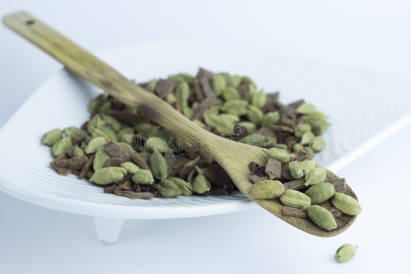 Kryddar kanel, cardamon, kryddnejlika på träskedreceptet som lagar mat kökkockkocken royaltyfri bild